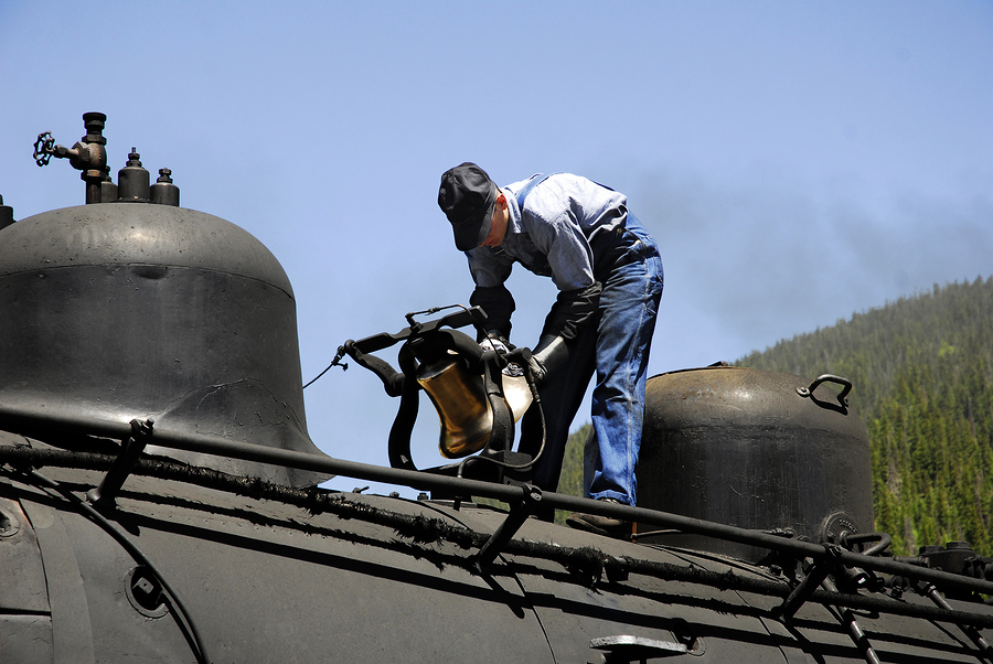 railroad worker inspecting train engine